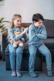 拿着玩具熊的女孩,当被触犯的男孩在家时坐沙发 图库摄影