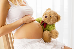 拿着玩具熊的孕妇对她的肚子 免版税图库摄影