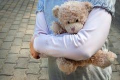 拿着玩具熊的孤独的女孩作为她的最好的朋友 库存图片