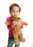 拿着玩具熊的害怕的女孩 图库摄影