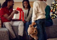 拿着玩具熊的小女孩观看 库存图片