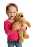 拿着玩具熊的微笑的女孩 免版税图库摄影