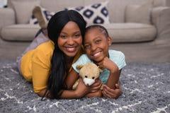 拿着玩具熊的母亲和女儿,当在家时说谎在地毯 免版税库存图片