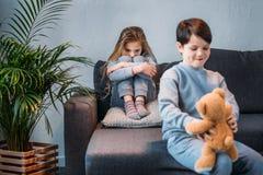 拿着玩具熊的狡猾的男孩,当被触犯的女孩坐沙发时 免版税库存照片