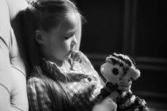 拿着玩具用她的手的哀伤的小女孩 库存照片