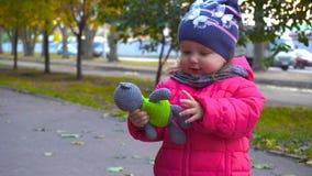 拿着玩具的可爱的女婴在秋天城市 股票视频