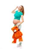 拿着玩具的睡衣的美丽的怀孕的白肤金发的妇女涉及白色背景 照片拍了  库存图片