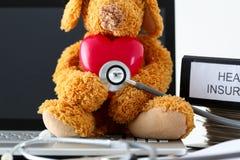 拿着玩具红色心脏的玩具熊听与phonendoscope头 图库摄影