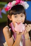 拿着玩具茶壶的逗人喜爱的女孩画象在生日聚会期间 库存图片