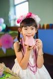 拿着玩具茶壶的逗人喜爱的女孩画象在生日聚会期间 库存照片
