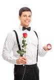 拿着玫瑰和定婚戒指的年轻人 免版税库存照片