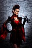 拿着玫瑰的一个新深色的夫人吸血鬼 库存照片