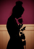 拿着玫瑰的妇女的阴影 库存图片