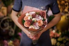 拿着玫瑰的惊人地美丽的花束女孩 库存图片
