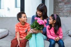 拿着玫瑰的愉快的母亲与她的儿子和女儿坐沙发 免版税库存照片