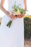 拿着玫瑰的美丽的婚礼花束一件白色礼服的新娘 免版税库存图片