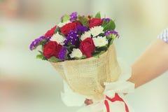 拿着玫瑰的花束妇女软的焦点手中为Valen 库存图片
