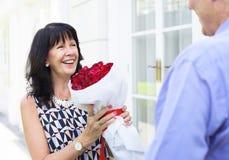 拿着玫瑰的花束资深妇女 库存照片