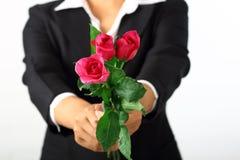 拿着玫瑰色花的妇女手 免版税库存图片
