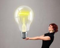 拿着现实3d电灯泡的美丽的夫人 库存照片