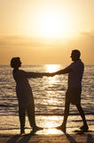 拿着现有量日落热带海滩的高级夫妇 免版税库存照片