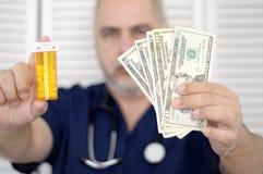 拿着现金和药片的医生 免版税库存图片