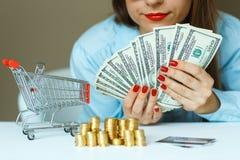 拿着现金,和在桌上的妇女是硬币,信用卡和 图库摄影