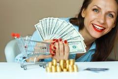 拿着现金,和在桌上的年轻微笑的妇女是硬币,哥斯达黎加 库存图片