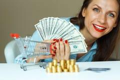 拿着现金,和在桌上的年轻微笑的妇女是硬币,哥斯达黎加 图库摄影