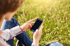 拿着现代巧妙的电话的少年学生男孩播种的射击,当坐在公园浏览互联网或传讯时的绿草 库存照片