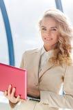 拿着现代红色膝上型计算机的衣服的愉快的成功的女商人 库存图片
