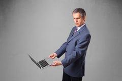 拿着现代膝上型计算机的英俊的商人 免版税库存图片
