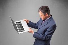 拿着现代膝上型计算机的英俊的商人 免版税库存照片