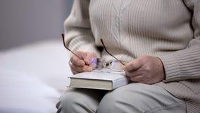 拿着玻璃和书,有趣的爱好,悠闲时间,智慧的资深妇女 库存照片