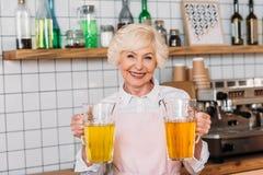 拿着玻璃瓶子柠檬水的愉快的资深咖啡馆工作者画象  免版税库存图片