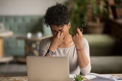 拿着玻璃的劳累过度的疲乏的非洲妇女感觉眼睛疲劳 免版税库存图片