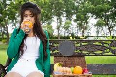 拿着玻璃,饮用的橙汁的少妇 免版税图库摄影