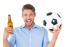 拿着球和啤酒的英俊的年轻人 图库摄影