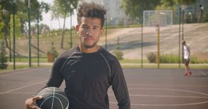拿着球和指向与他的手指的年轻英俊的非裔美国人的男性篮球运动员特写镜头画象  股票录像