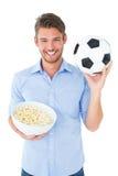 拿着球和玉米花的英俊的年轻人 免版税库存图片