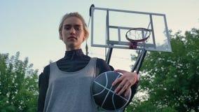 拿着球和看照相机的美丽的年轻女性蓝球运动员,站立在公园,低角度 股票视频