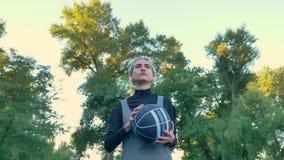 拿着球和走在公园,低角度,佩带的运动服的确信的白肤金发的女性蓝球运动员 股票录像