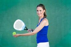 拿着球拍paddleball和服务球的妇女 女运动员 免版税库存照片