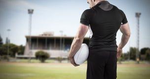 拿着球的困难的橄榄球球员的综合图象 图库摄影
