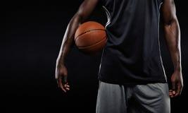 拿着球的美国黑人的蓝球运动员 免版税库存图片