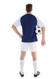 拿着球的蓝色球衣的足球运动员 库存图片