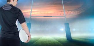 拿着球的被转动的橄榄球球员的综合图象 免版税库存图片