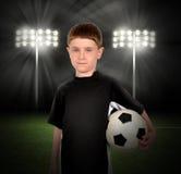拿着球的足球男孩在体育场内 免版税库存图片