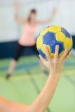 拿着球的运动员反对手球目标 免版税图库摄影