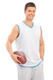 拿着球的年轻男性足球运动员 免版税库存图片